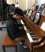 Boy playing piano in music class