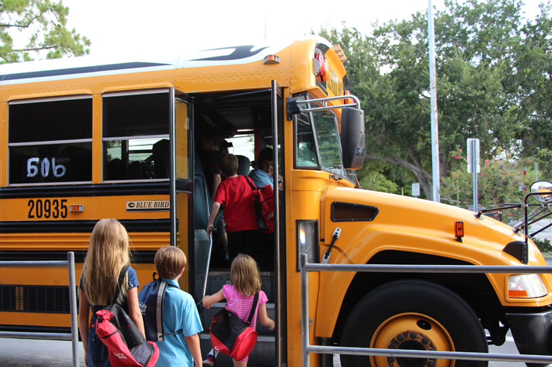 Students getting onto a school bus.