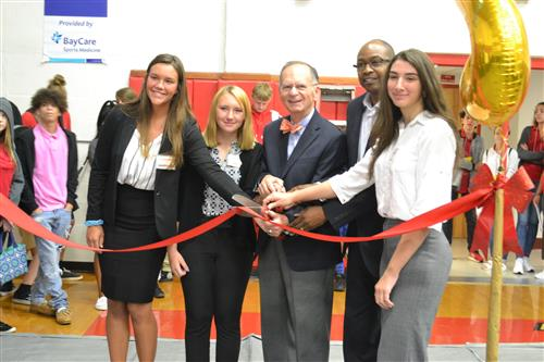 students at a ribbon cutting with the mayor and assistant principal
