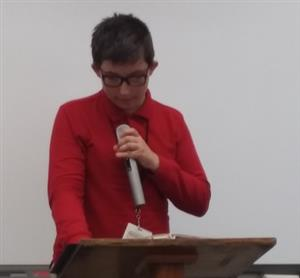 Middle school student holds a microphone while reciting a poem.