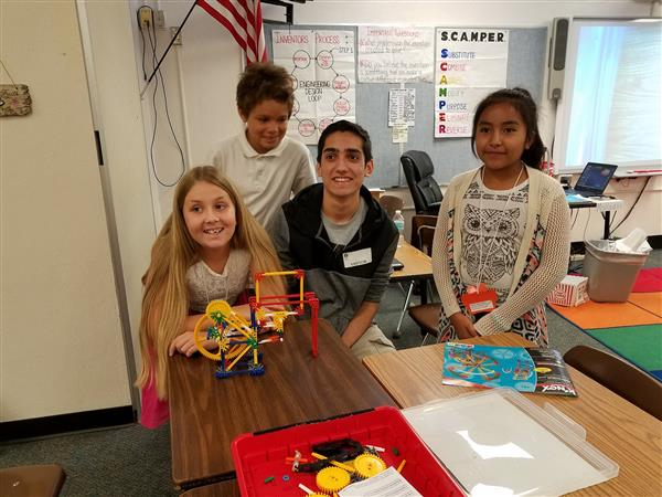 High school student helping elementary students with science project