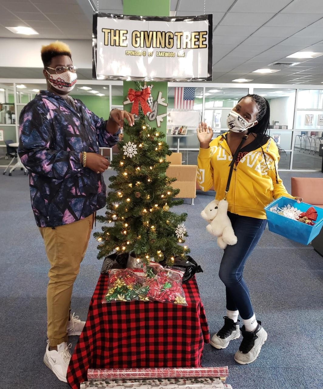 "Two students stand on front of the ""Giving Tree."""