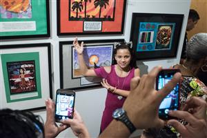 Student shows off her artwork at the Word & Image Exhibit