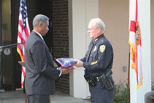 Luke Williams accepts American flag from outgoing Chief Rick Stelljes.
