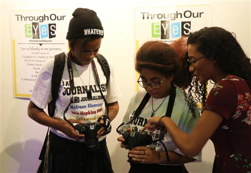Lakewood High students view photos on a camera.