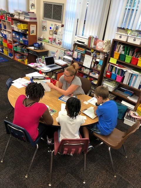 Teacher works with students to improve reading skills