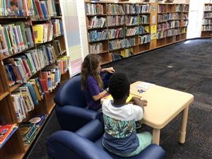 A fifth grade student helps a first grade student with literacy skills